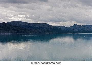 La vista de las montañas y los fiordos, nublada