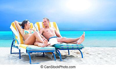 La vista de una pareja en una silla de cubierta se relaja en la playa
