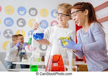 Las colegialas optimistas buscan la reacción química deseada en frascos