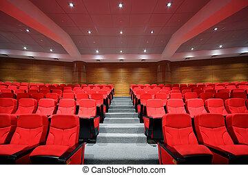 Las filas de las sillas rojas están en el pasillo vacío