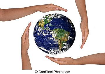 Las manos alrededor de una vista satelita de la tierra