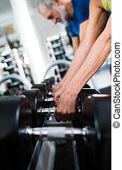 Las manos de la pareja senior en el gimnasio haciendo ejercicio con pesas