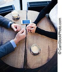 Las manos de mujer de negocios y hombre de negocios sobre la mesa