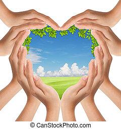 Las manos hacen que la forma del corazón cubra la naturaleza