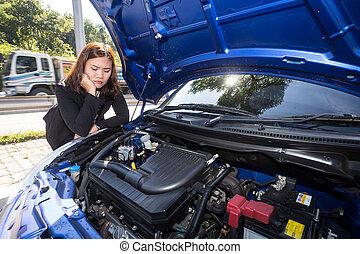 Las mujeres asiáticas abrieron el capó y vieron un motor de coche roto en la calle