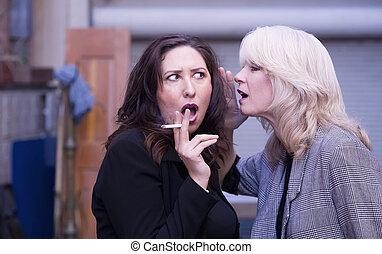 Las mujeres chismean durante una pausa para fumar