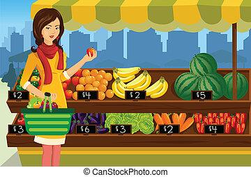 Las mujeres compran en un mercado de granjeros
