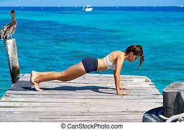 Las mujeres latinas hacen ejercicio en el muelle de playa