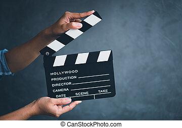 Las mujeres toman el tablero de clapper para hacer cine en el estudio.