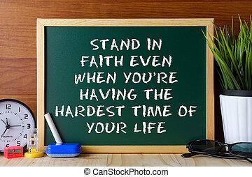 Las palabras se mantienen en la fe incluso cuando estás pasando el peor momento de tu vida escrito en una pizarra verde en la mesa de madera.