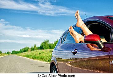 Las piernas de la mujer salen de la ventana del auto. Concepto de un viaje sin preocupaciones.