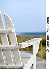 Las sillas Adirondack apuntan hacia el océano.