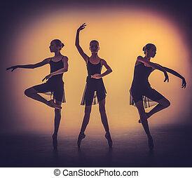 Las siluetas de jóvenes bailarines de ballet posando en un backgro gris