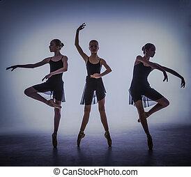 Las siluetas de jóvenes bailarines de ballet posando en un fondo gris.