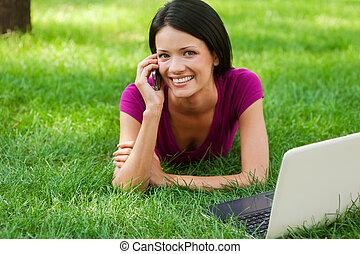 Las tecnologías hacen la vida más fácil. Una joven atractiva que habla por teléfono y sonríe mientras está en la hierba con una laptop cerca