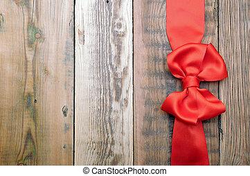 Lazo rojo y cinta en el pasado de madera