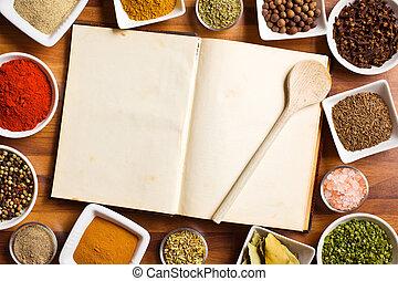 Libro de cocina y varias especias y hierbas.