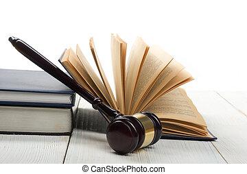Libro de leyes abierto con martillos de madera en una mesa en un tribunal