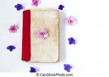 Libro de papel antiguo y flores sobre fondo blanco.