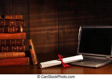 Libros anticuarios, diploma con portátil sobre el escritorio