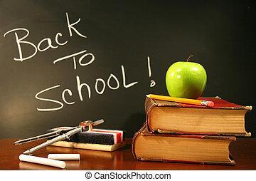 Libros escolares con manzana sobre el escritorio