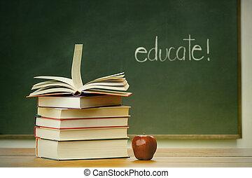 Libros escolares y manzanas en el escritorio