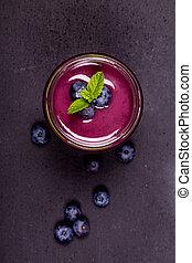 Licuado de arándano en un frasco de vidrio con bayas frescas y guarnición de menta, en un fondo de pizarra