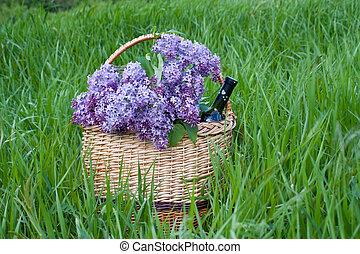 Lila en una canasta con una botella de vino, parada sobre hierba verde
