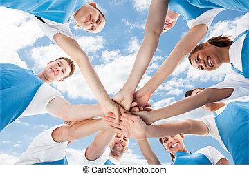 Limpiadores profesionales amontonando las manos contra el cielo