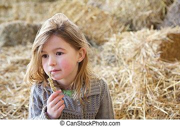 Linda chica sentada sola en pajares
