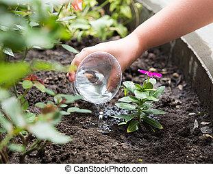 Linda niña regando plantas en el jardín