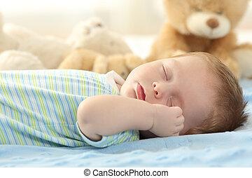 Lindo bebé durmiendo en una cama