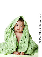 Lindo bebé sentado entre una manta verde.