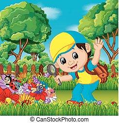 Lindo niño sosteniendo una lupa en un jardín de flores
