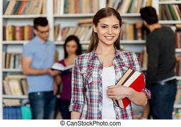 Listo para su examen final. Hermosa joven sosteniendo libros en su mano y sonriendo a la cámara mientras otras tres personas de pie detrás de ella y cerca de la estantería