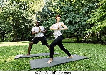 lleno, atlético, yoga, ropa de deporte, pareja, trabajando, mientras, parque, retrato, verde, mujer, longitud, o, tenencia, hombre, multiétnico, afuera, juntos, palmas