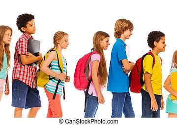 Los chicos de la escuela hacen fila con vistas al perfil de mochilas