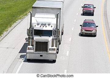 Los coches pasan camiones en la interestatal