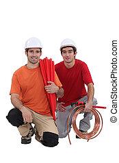 Los comerciantes de rodillas tienen materiales y herramientas