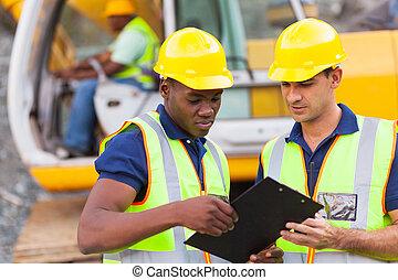 Los compañeros de construcción discuten sobre el plan de trabajo