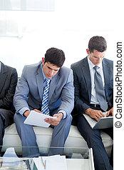 Los empresarios concentrados esperan una entrevista de trabajo en una oficina