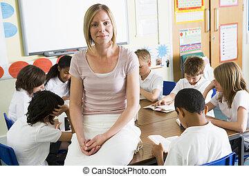 Los escolares y su maestra leen libros en clase
