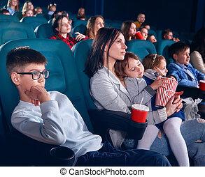 Los espectadores en el cine ven películas con ojos firmes.