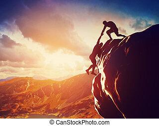 Los excursionistas escalan en roca, montaña