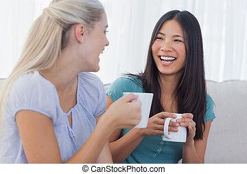 Los jóvenes amigos se ponen al día con tazas de café