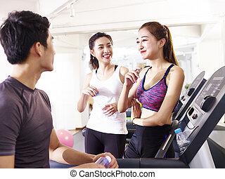 Los jóvenes asiáticos charlando en el gimnasio