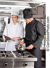 Los jóvenes chefs con tablas digitales preparando comida