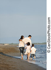 Los jóvenes felices se divierten en la playa al atardecer