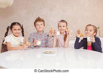 Los niños beben leche con galletas