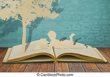 Los niños en papel leen un libro